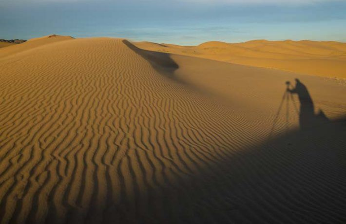 Photographers shadow in Khongor Sand Dune, Govi Gurvan Saikhan National park, (Three Beauty Mountain National Park) Gobi desert, Umnugovi province, South Mongolia.